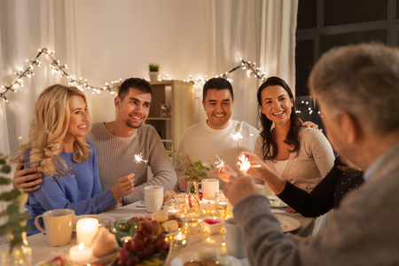 celebration, holidays and christmas concept - happy family with sparklers having fun at dinner party at home Stock Photo