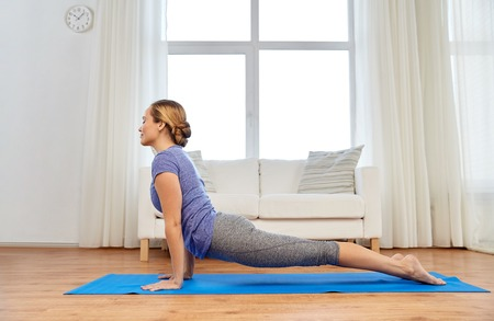 fitness, sport and healthy lifestyle concept - woman doing yoga upward-facing dog pose on mat at home Stock Photo