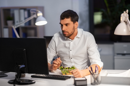 business, overwork, deadline and people concept - businessman with computer eating at night office