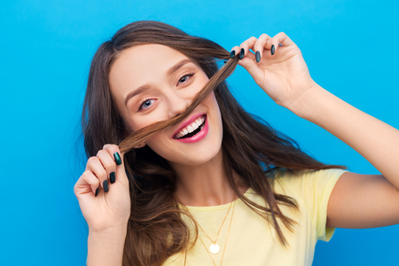 emotions, expressions, hairstyle and people concept - smiling young woman or teenage girl making mustache with strand of hair over bright blue background Banco de Imagens