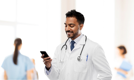 smiling indian male doctor with smartphone Standard-Bild