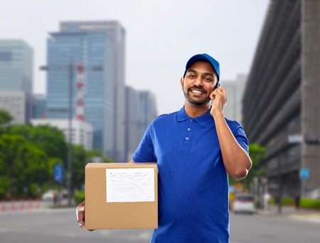 indian delivery man with smartphone and parcel box Stock Photo