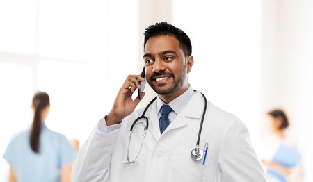smiling indian male doctor calling on smartphone