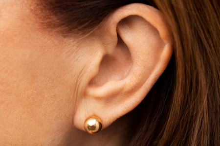 close up of senior woman ear with golden earring