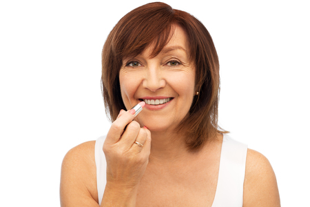 smiling senior woman applying lipstick to her lips