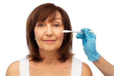 senior woman and surgeon hands with scalpel Foto de archivo - 117391094