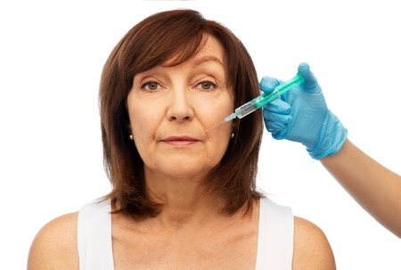 senior woman and surgeon hand with syringe Stock Photo