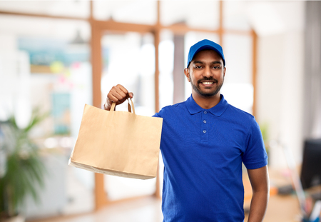 delivery man with food in paper bag at office