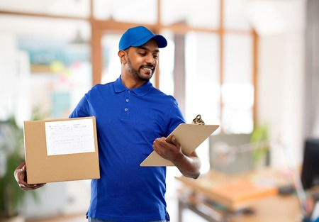 delivery man with parcel and clipboard at office Stock Photo