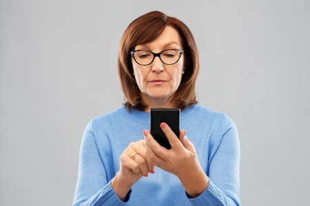 senior woman in glasses using smartphone