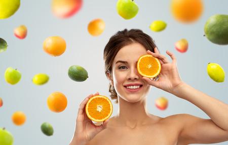 lächelnde Frau mit Orangen über Früchtehintergrund