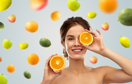smiling woman with oranges over fruits background 版權商用圖片 - 117393907