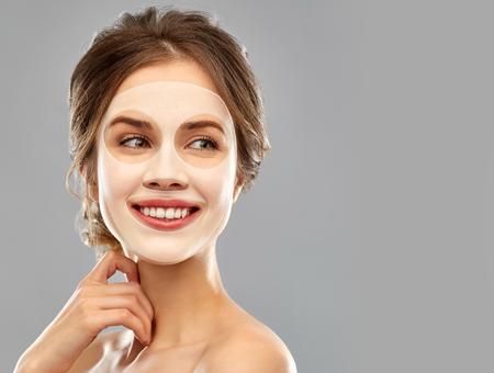 jeune femme souriante portant un masque facial en feuille