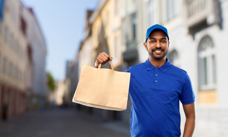 indian delivery man with food in paper bag in city