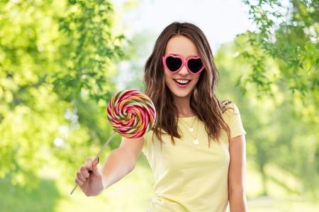 teenage girl in sunglasses with lollipop 스톡 콘텐츠