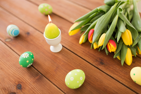 candle in shape of easter egg and tulip flowers