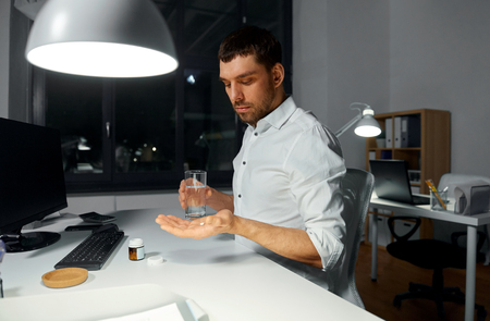 businessman taking medicine pill at night office Stok Fotoğraf
