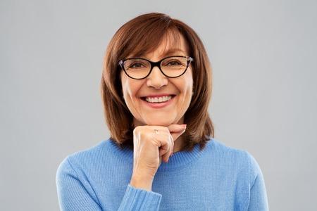 portrait of senior woman in glasses over grey Banco de Imagens