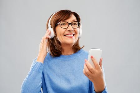 senior woman in headphones listening music on cell Foto de archivo