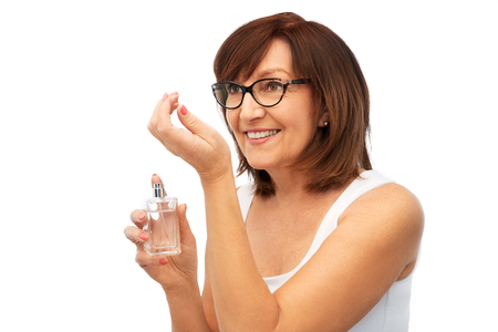 senior woman smelling perfume from her wrist Stock Photo
