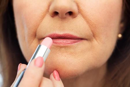 close up of senior woman applying lipstick