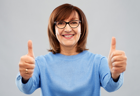 portrait of senior woman showing thumbs up