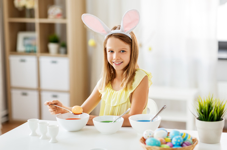girl coloring easter eggs by liquid dye at home Stock Photo