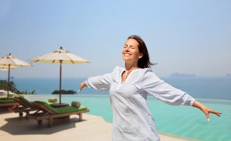 happy woman enjoying sun over infinity edge pool Stock Photo