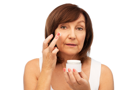 senior woman applying cream to her face