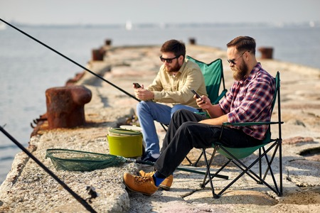 friends with smartphones fishing on pier at sea