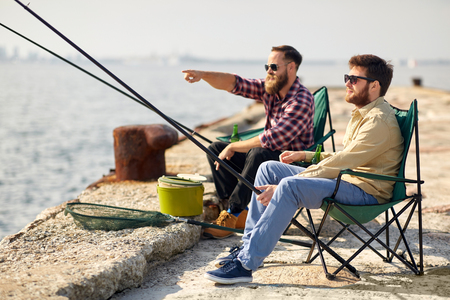 happy friends with fishing rods on pier Stock fotó