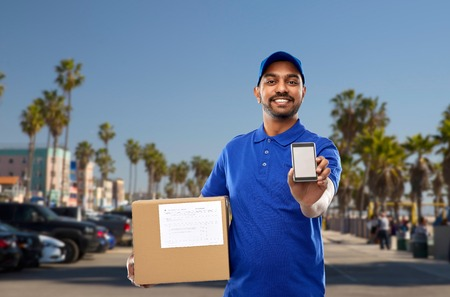indian delivery man with smartphone and parcel box Banque d'images - 117751568