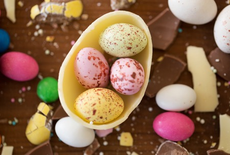 chocolate egg and candy drops on wooden table