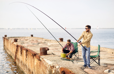 happy friends with fishing rods on pier Stock Photo