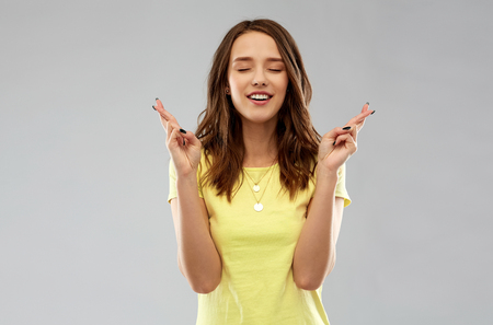 young woman or teenage girl with fingers crossed