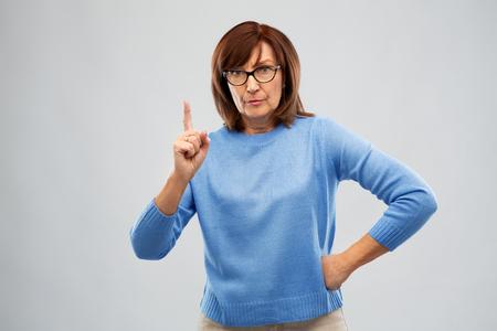 displeased senior woman in glasses warning