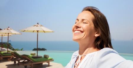 happy woman enjoying sun over infinity edge pool 写真素材