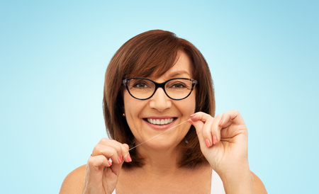 senior woman cleaning her teeth by dental floss Stock Photo