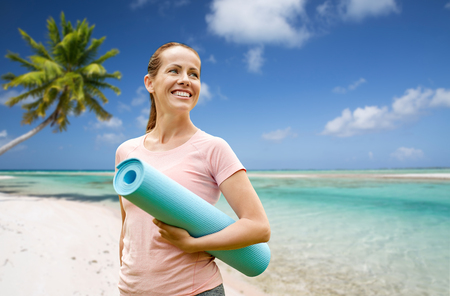 happy smiling woman with exercise mat over beach Stock Photo