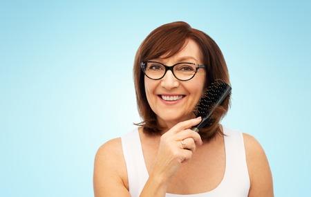 portrait of senior woman in glasses brushing hair Stockfoto