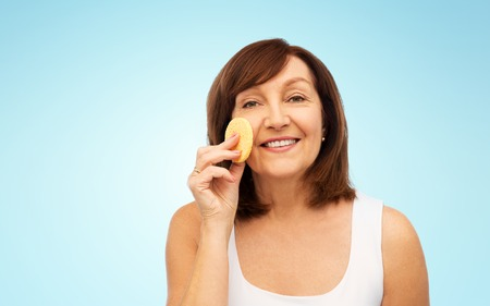 woman cleaning face with exfoliating sponge Фото со стока