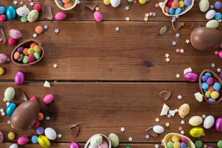 chocolate eggs and candy drops on wooden table Stock Photo