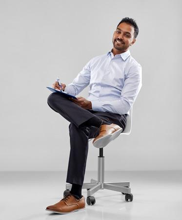 homme d'affaires indien souriant écrivant au presse-papiers Banque d'images
