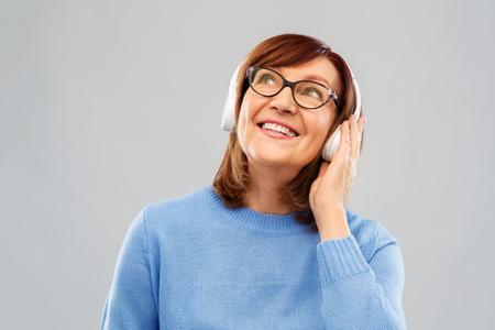 senior woman in headphones listening to music Stock fotó