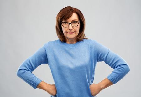 Mujer mayor enojada en vasos sobre fondo gris Foto de archivo