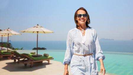 happy woman walking over infinity edge pool