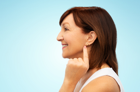 smiling senior woman pointing to her earring