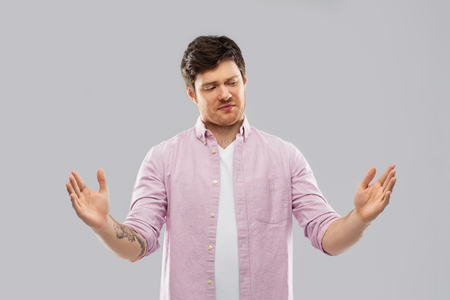 displeased young man showing size of something Stock Photo