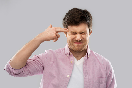 man making headshot by finger gun gesture Stock Photo