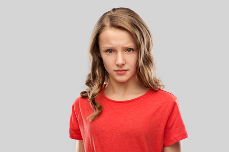 sad or angry teenage girl in red t-shirt